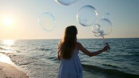 Dziewczyny dmuchanie gulgocze na plaży w zwolnionym tempie Młoda dziewczyna dmucha mydlanych bąble w wieczór, podczas zmierzchu B zbiory