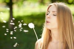 Dziewczyny dmuchanie na dandelion Zdjęcie Royalty Free
