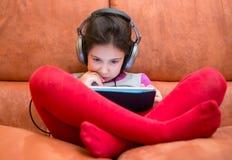 Dziewczyny dopatrywania pastylki komputer osobisty z hełmofonami Zdjęcie Stock