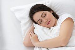 Dziewczyny dosypianie na białym łóżku fotografia stock