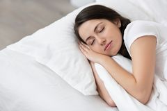 Dziewczyny dosypianie na białym łóżku obraz stock