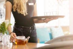 Dziewczyny dzia?anie jako kelnerka trzyma tac? z herbat? obraz stock