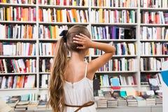 Dziewczyny dziecko intrygował wybór książki w sklepie Obraz Royalty Free