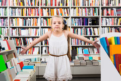 Dziewczyny dziecko intrygował wybór książki w sklepie Zdjęcie Royalty Free