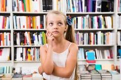 Dziewczyny dziecko intrygował wybór książki w sklepie Zdjęcia Royalty Free