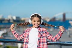 Dziewczyny dziecko słucha muzykę outdoors z nowożytnymi hełmofonami Słucha dla bezpłatnego Dostaje muzyczną rodzinną prenumeratę  zdjęcie stock
