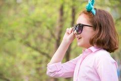 Dziewczyny dziecko w różowej koszula i okularach przeciwsłonecznych w naturze fotografia royalty free