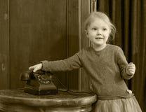 Dziewczyny dzwoni na starym telefonie Zdjęcie Royalty Free