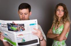 dziewczyny faceta gazetowy czytelniczy piłki nożnej spęczenie zdjęcia royalty free