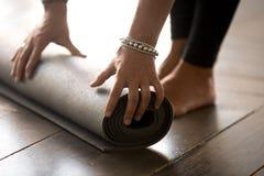 Dziewczyny falcowanie lub unrolling sprawności fizycznej mata dla joga medytaci zdjęcie stock