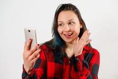 Dziewczyny falowanie na mądrze telefonie podczas gdy podczas wideo wezwania odizolowywającego na białym tle obrazy stock