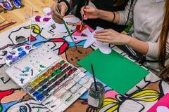 Dziewczyny farby kolory przy stołem W rękach muśnięcie Kolor paleta z farbami zdjęcie stock