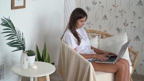Dziewczyny freelancer siedzi w słomianym krześle i pracuje z laptopem w domu, zwolnione tempo zbiory wideo