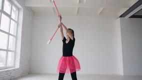 Dziewczyny gimnastyczka wiruje buławy Dziewczyny gimnastyczka z buławą w ręce krąży wokoło ona w sport szkole w białym tle zbiory