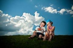 Dziewczyny i chłopiec obsiadanie na trawie na trawie fotografia stock