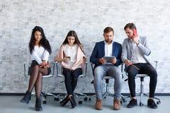 Dziewczyny i faceci siedzą na krzesłach Everyone angażuje w jego swój biznesie zdjęcia stock