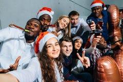 Dziewczyny i faceci w Santa kapeluszach robi selfie przy przyjęciem Boże Narodzenia, nowego roku pojęcie fotografia royalty free