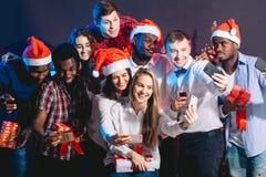 Dziewczyny i faceci w Santa kapeluszach robi selfie przy przyjęciem Boże Narodzenia, nowego roku pojęcie zdjęcie stock
