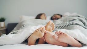 Dziewczyny i facetów cieki dotyka w łóżku pod koc podczas gdy ludzie kłama wpólnie zbiory
