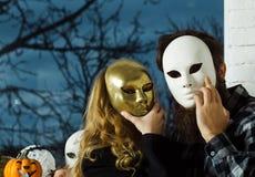 Dziewczyny i mężczyzna kryjówki twarz z masque zdjęcia stock