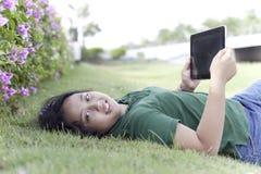 Dziewczyny i pastylki komputer na zielonej trawie Fotografia Royalty Free
