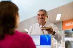 Dziewczyny i starszego mężczyzna oddawanie rezerwuje w bibliotece Zdjęcia Stock
