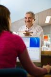 Dziewczyny i starszego mężczyzna oddawanie rezerwuje w bibliotece Fotografia Stock