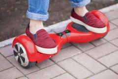 Dziewczyny jazda na nowożytny czerwony elektryczny mini segway lub unosi się deskową hulajnoga fotografia stock