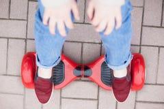 Dziewczyny jazda na nowożytny czerwony elektryczny mini segway lub unosi się deskową hulajnoga obrazy stock
