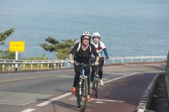 Dziewczyny jeździć na rowerze ciężki na drodze Zdjęcie Stock