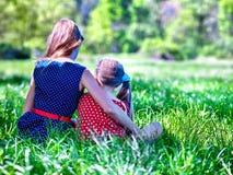 Dziewczyny jest ubranym czerwonego i błękitnego polek kropek smokingowego obsiadanie na zielonej trawie w parka Zdjęcie Stock