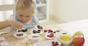 Dziewczyny kładzenia jagody na muffins na stole zbiory wideo