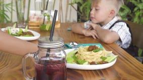 Dziewczyny kelnerki porcji małe dzieci przy restauracja stołem Chłopiec i dziewczyna dostaje jedzenie w kawiarni Szczęśliwy dziec zdjęcie wideo