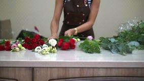 Dziewczyny kwiaciarnia rozkłada na desktop pięknych kwiatach zbierać one w bukiecie, mały biznes zbiory wideo