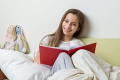 Dziewczyny 10 lat siedzi w domu w łóżku z szkolnym notatnikiem, czytaniu i uczenie, narządzanie dla szkoły w domu obrazy royalty free