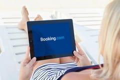 Dziewczyny lying on the beach basenu i mienia ipad z app rezerwacją na Fotografia Stock
