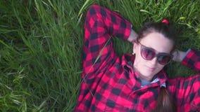 Dziewczyny lying on the beach i odpoczywać na gazonie na słonecznym dniu w parku na trawie Kobieta na trawie w czerwieni i czerni zbiory wideo