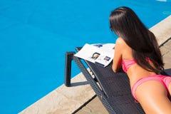 Dziewczyny lying on the beach na deckchair i czytelniczym magazynie obrazy stock