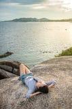 Dziewczyny lying on the beach na falezie nad nadmorski przy zmierzchem Fotografia Royalty Free