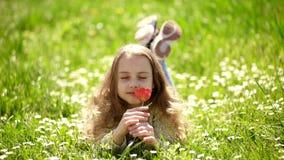 Dziewczyny lying on the beach na trawie, grassplot na tle Tulipanowy woni poj?cie Dziewczyna na u?miechni?tych twarz chwyt?w czer zbiory wideo