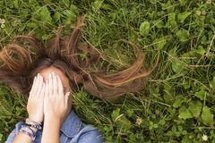 Dziewczyny lying on the beach na zielonej trawie zakrywa jego twarz z jego ręki Obrazy Stock