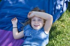 Dziewczyny lying on the beach w parkowy przyglądającym i ono uśmiecha się z ręką w głowie Zdjęcie Stock