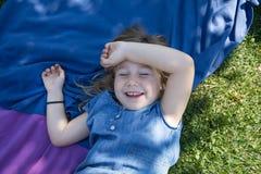 Dziewczyny lying on the beach w parku śmia się z zamkniętymi oczami Zdjęcia Stock