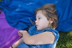 Dziewczyny lying on the beach w parku z rozważną twarzą Zdjęcie Royalty Free
