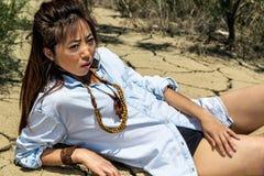 Dziewczyny lying on the beach w pustyni z krakingową ziemią Obraz Stock