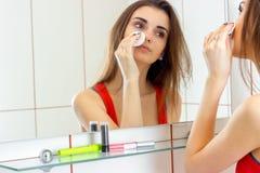 Dziewczyny młodzi atrakcyjni spojrzenia w pocieraniach i lustrze twój twarz z bawełnianym dyskiem Obrazy Stock