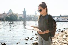 Dziewczyny młodzi piękni stojaki i spojrzenia przy mapą obok Vltava rzeki z zadziwiającą starą architekturą Praga Obraz Royalty Free