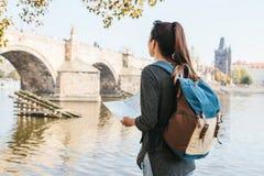 Dziewczyny młodzi piękni stojaki i spojrzenia przy mapą obok Vltava rzeki z zadziwiającą starą architekturą Praga Obrazy Stock