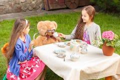 Dziewczyny ma herbacianego przyjęcia z misiem przy jardem Zdjęcia Royalty Free