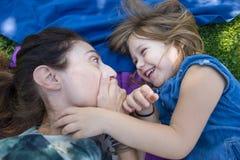 Dziewczyny matka i śmiać się zaskakiwaliśmy twarzy lying on the beach w parku Fotografia Stock
